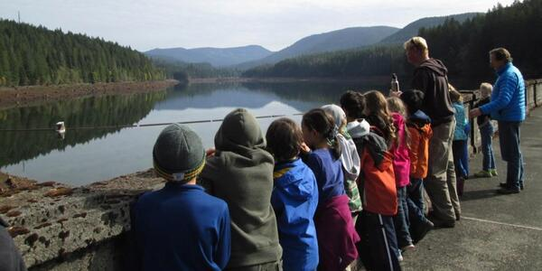 Photo of a class of young kids with their backs to us looking over the side of a concrete dam looking at a calm body of water with green mountains in the background.
