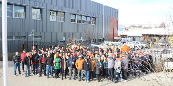 Dozens of water bureau team members pose in front of a building