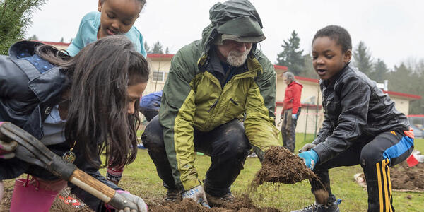 A volunteer kneels down to help three kindergartners dig soil out of a tree planting hole.