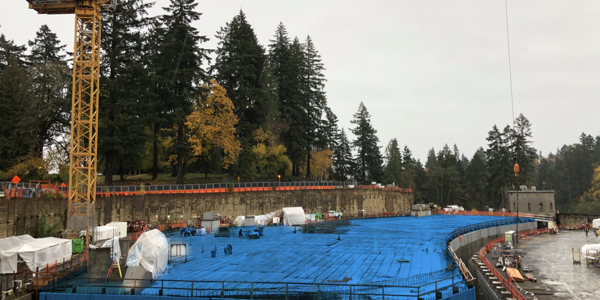 This photograph shows the Washington Park Reservoir construction site. The reservoir itself has been highlighted in blue to make it stand out from the rest of the construction site.