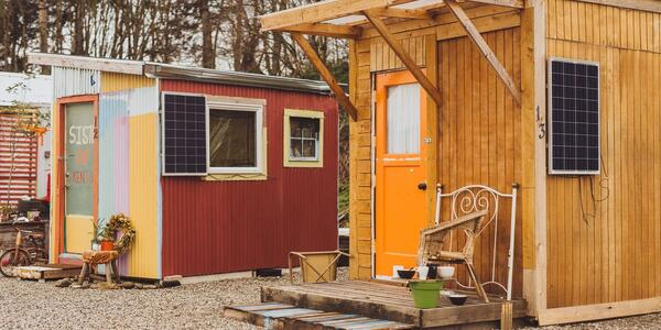 Two tiny homes with colorful paint and pallets for front porches