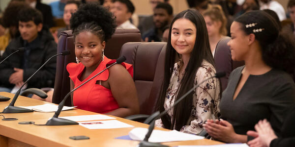 Three Multnomah Youth Council members speak at a table during their 2019-20 Swearing in Ceremony