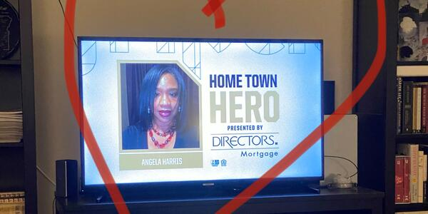 A picture of a TV screen with Water bureau employee Angie Harris on it, and a large red heart drawn on the picture over it