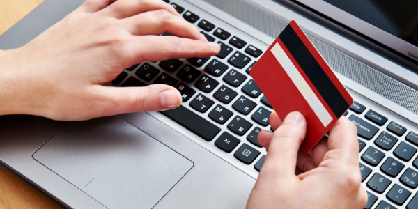 Photograph of a person typing on a laptop with one hand and holding a credit card in the other hand.