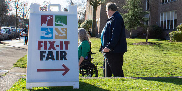 Man with cane and woman in wheelchair walking behind Fix-It Fair sign