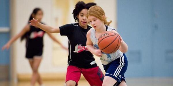 A young basketball player dribbles the ball while a defender follows closely.