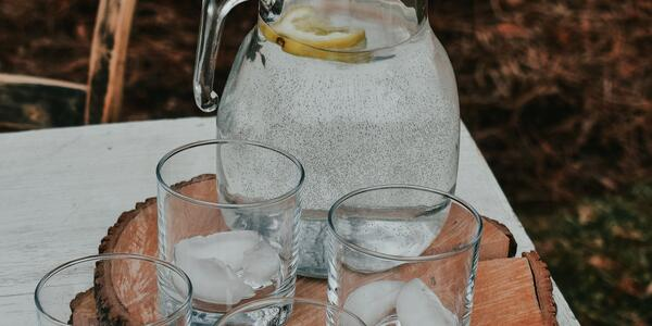 picture of a glass jar full of water and four glasses sitting on a cookie of a tree trunk