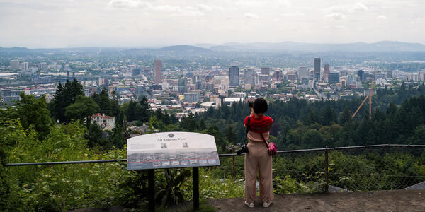 A visitor at the Pittock Mansion takes a photo of the Portland skyline.