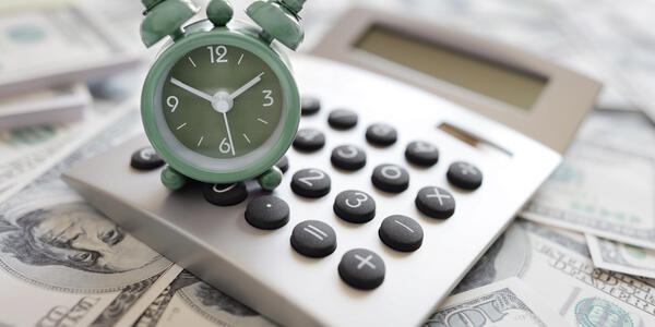 image of dollar bills laid out with a calculator on top and a tiny clock on top of the calculator.