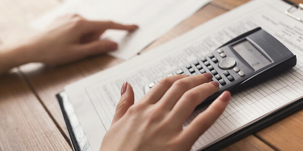 close up of a hand on a table reviewing paperwork with a calculator under the right hand