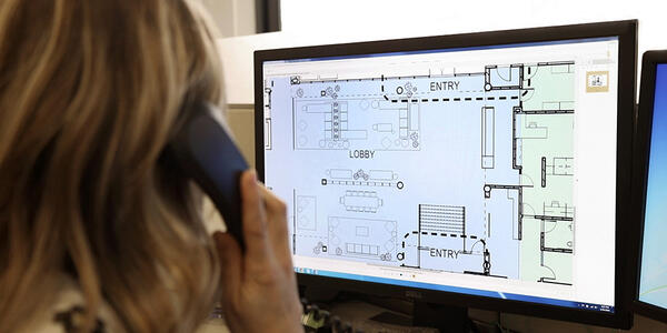 Woman looks at building plans on a computer screen while on the phone.
