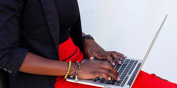 Close up photograph of person wearing a red skirt, holding a laptop on their lap