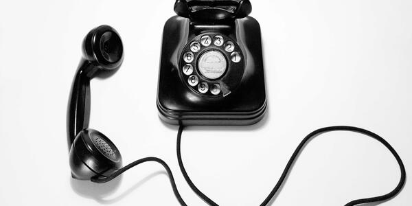 black rotary telephone against a white background