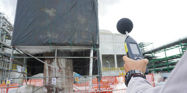 Person holding a sound meter in front of a construction site.