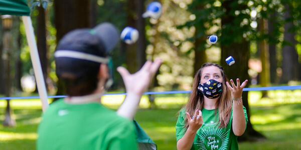 Two PP&R staff members wearing green t-shirts juggle footbags outside in the park.