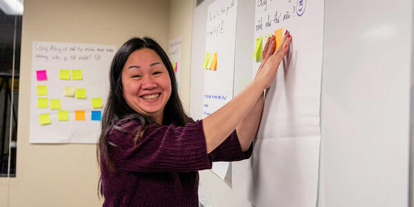 Woman smiling for the camera as she adds sticky notes to a whiteboard during a community work session.