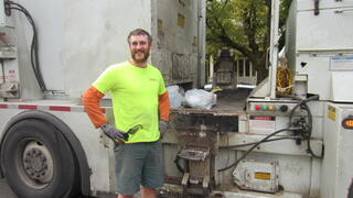 A garbage truck driver in a yellow shirt, standing in front of their truck