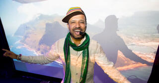A photo of DJ Prashant singing and smiling: He has a dark beard and mustache, is wearing a green scarf and multi-colored baseball cap. He is wearing a headset and looking at the camera.