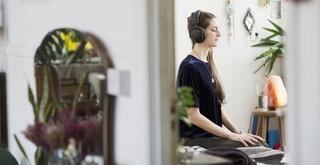 Woman meditates at home with eyes closed and headphones on