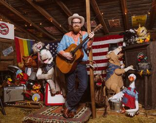 Andy, from Red Yarn Productions, performing a song surrounded by puppets in a Country Western setting