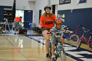 In a gym, a woman and a child ride a bike while smiling. In the background is a man fixing a bike. There are also other bikes in the picture waiting for a rider.