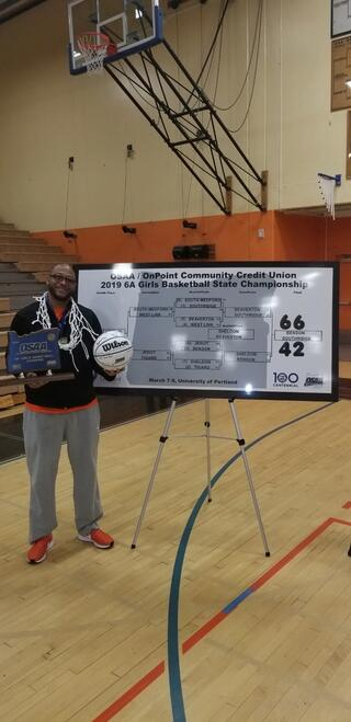 "Coach Dexteur standing by a sign of that reads ""OSAA/OnPoint Community Credit Union - 2019 6A Girls Basketball State Championship"""""