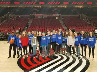 Basketball team (all girls) is standing on the Blazer Court in Portland