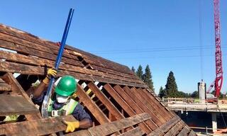 Worker deconstructing house roof.