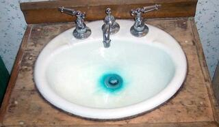 Photo of a white bathroom sink with blue staining at the bottom.