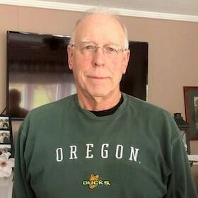 "Robert ""Bob"" Price gives a closed lip smile wearing a dark green Oregon Ducks sweatshirt in his living room."