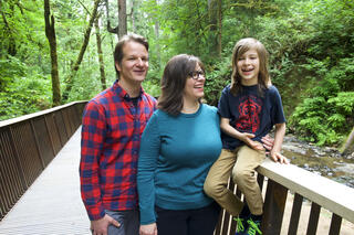 Mike in a red plaid shirt and Bryna in a blue sweater standing on a bridge with their son Holden who is sitting on the bridge railing.