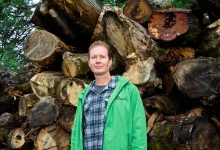 Man in green jacket and plaid shirt stands in front of pile of wood