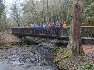 20 people standing on a bridge cover a creek in a natural area