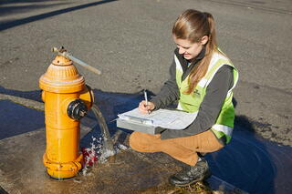 Photo of a woman wearing a yellow safety vest next to an orange hydrant that has water flowing out of it. The woman is writing notes on a metal clipboard.