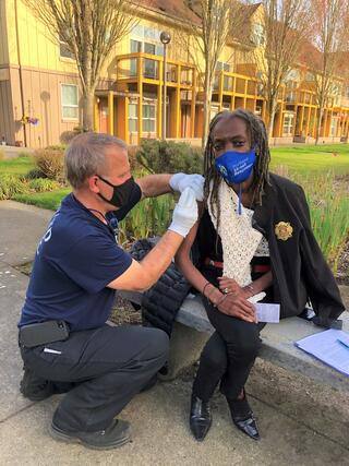 Commissioner Jo Ann Hardesty is sitting down wearing a Portland Fire & Rescue Coat. To her left, a Portland Firefighter in a blue t-shirt is administering the 1st shot of a COVID-19 vaccine.