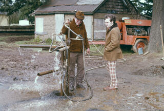 Old photo of two men - one is wearing amazing red and white plaid pants - standing in a muddy area looking at pipes coming out of a groundwater pump in the ground. Water is splashing out of the pipes and onto the ground.