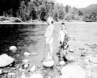 Scanned black and white historical image of three kids standing in a river dipping nets in the water trying to catch fish.