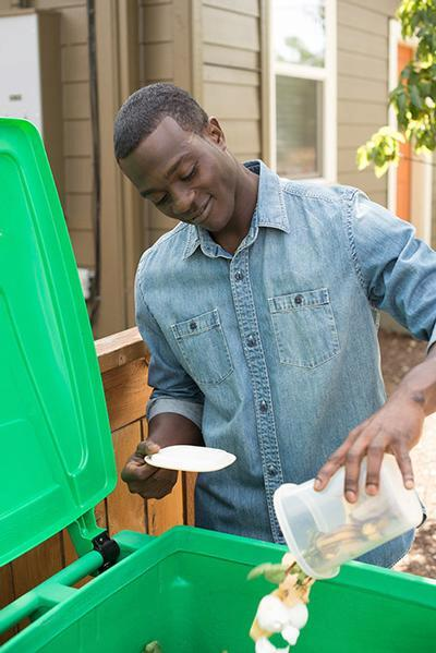 A person putting food scraps in a green composting cart