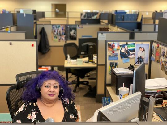Teresa Solano sits at a very busy desk with multiple monitors.  Teresa is surrounded by empty cubicles.