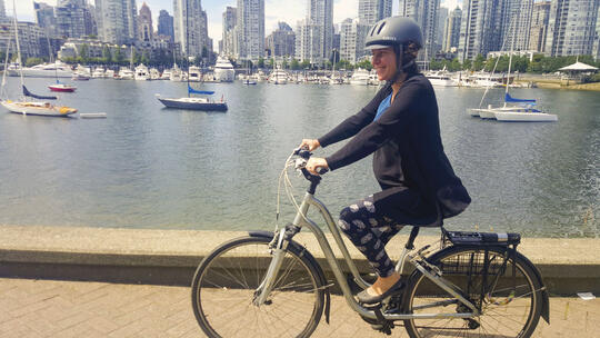 Pregnant woman riding bike along waterfront path