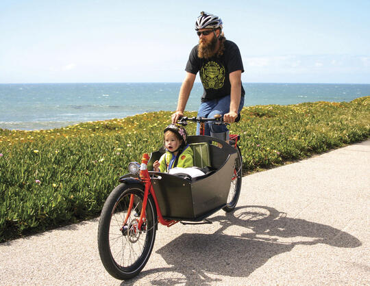Bicyclist riding with child in front cargo on beach path