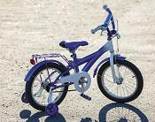 Small purple bike with training wheels on dirt ground