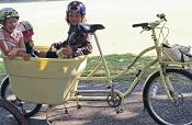 Children riding in cargo bike bucket on yellow bike