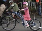 Child in pink dress riding on tag-along bicycle