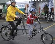 Parent and child ride tandem bike in at a market