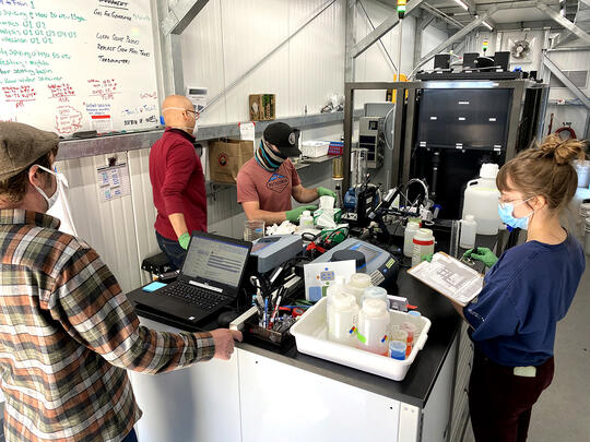 Image of three men and one woman with face masks on in a lab environment inside the pilot facility