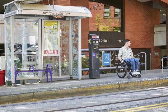 A person in a wheelchair waits at a Portland Streetcar stop. Photo by PBOT.