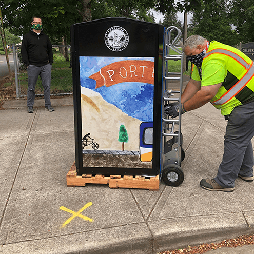 Man wearing safety vest installing painted public trash can