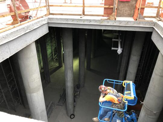 A photo looking down through a hole in the roof of the concrete reservoir. You can see concrete columns holding up the roof and a worker in blue machinery suspended over forty feet in the air looking down into the reservoir.