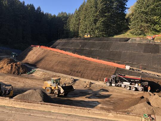 "Photo of large trucks and earthmoving equipment sitting at the bottom of a hillside. The hillside has been covered in black plastic known as ""geocells."" Some of the geocells are light brown in color because they have been filled with dirt."